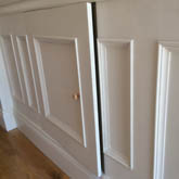 close up of secret wall panelled  cupboard within panelling design made in Britain by wall panelling experts in the uk